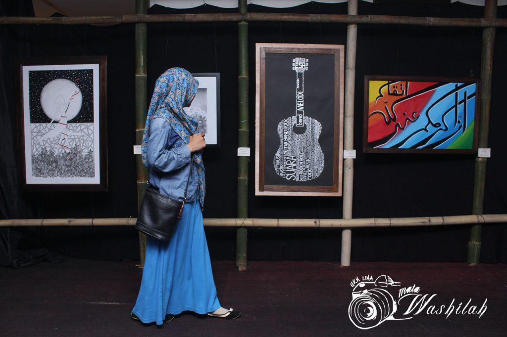 "Seorang mahasiswa berjalan sambil memperhatikan hasil seni rupa pada Eksibisi Eksibanat XIX Unit Kegiatan Mahasiswa (UKM) Seni Budaya (SB) eSA di Pusat Kegiatan Mahasiswa (PKM). Kamis (26/05/2016). Tema yang diusung dalam acara ini ialah ""seNilai Berkarya""."