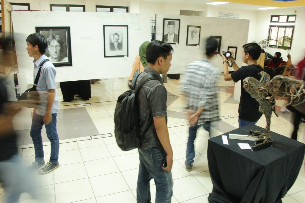 Pengunjung melihat seni rupa yang dipamerkan di pameran rupa se UKM Seni Makassar di Perpustakaan. Selasa, 1 November 2016. Pameran ini berlangsung selama tiga hari yakni Selasa sampai Kamis 3 November 2016.