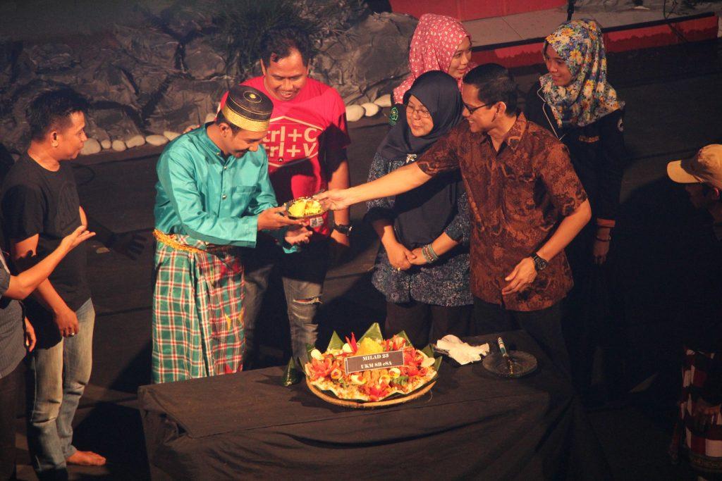 Pendiri UKM SB eSA Zulfahmi Alwi memberikan nasi tumpeng kepada Muh Kurniadi Asmi sebagai simbol milad UKM Seni yang telah berusia 23 tahun di gedung PKM. Sabtu, 19 November 2016.